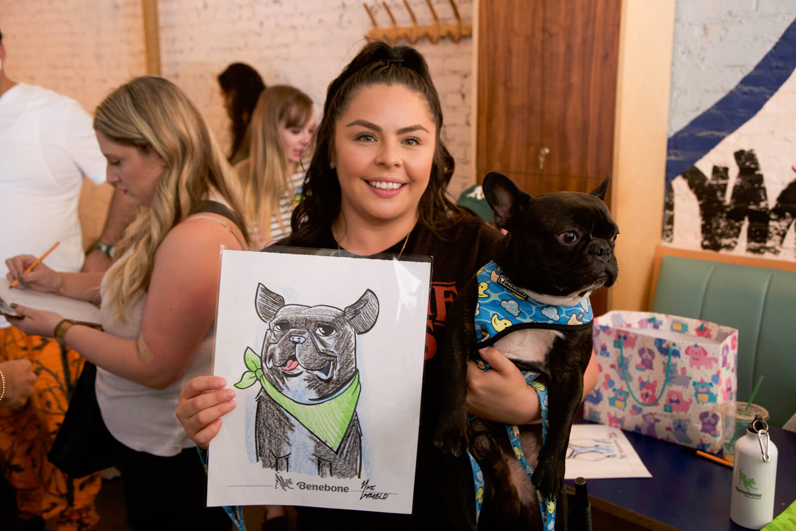 Women holding dog and cartoon drawing of dog